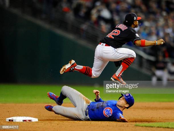 Shortstop Francisco Lindor of the Cleveland Indians leaps over pinch runner Chris Coghlan of the Chicago Cubs to make an out in the ninth inning of...
