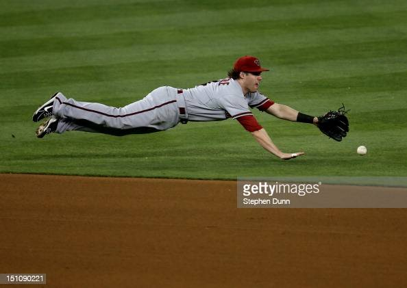 Shortstop Jake Elmore of the Arizona Diamondbacks dives but can't catch a single hit by AJ Ellis of the Los Angeles Dodgers in the fourth inning on...