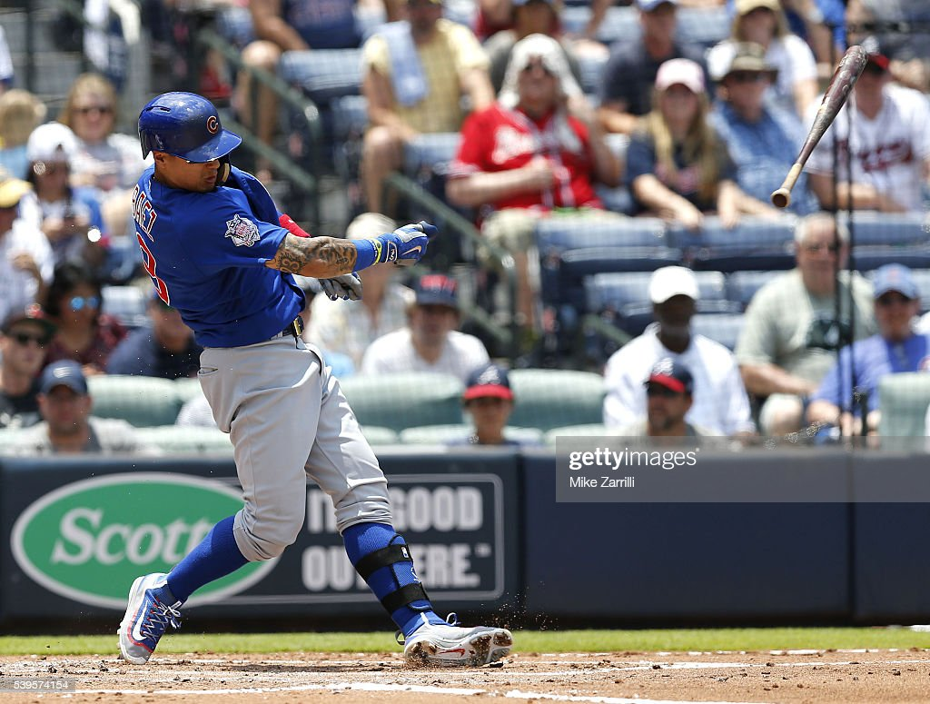 Shortstop Javier Baez of the Chicago Cubs loses control of his bat while swinging in the second inning during the game against the Atlanta Braves at...