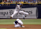 Shortstop Jean Segura of the Milwaukee Brewers leaps over Curt Casali of the Tampa Bay Rays after getting the force out at second base on a fielder's...