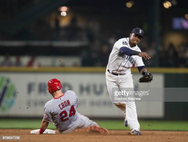 Shortstop Jean Segura of the Seattle Mariners turns a double play after forcing out CJ Cron of the Los Angeles Angels of Anaheim at second base on a...