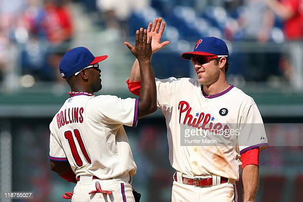 Shortstop Jimmy Rollins and second baseman Chase Utley of the Philadelphia Phillies highfive after winning a game against the Atlanta Braves at...
