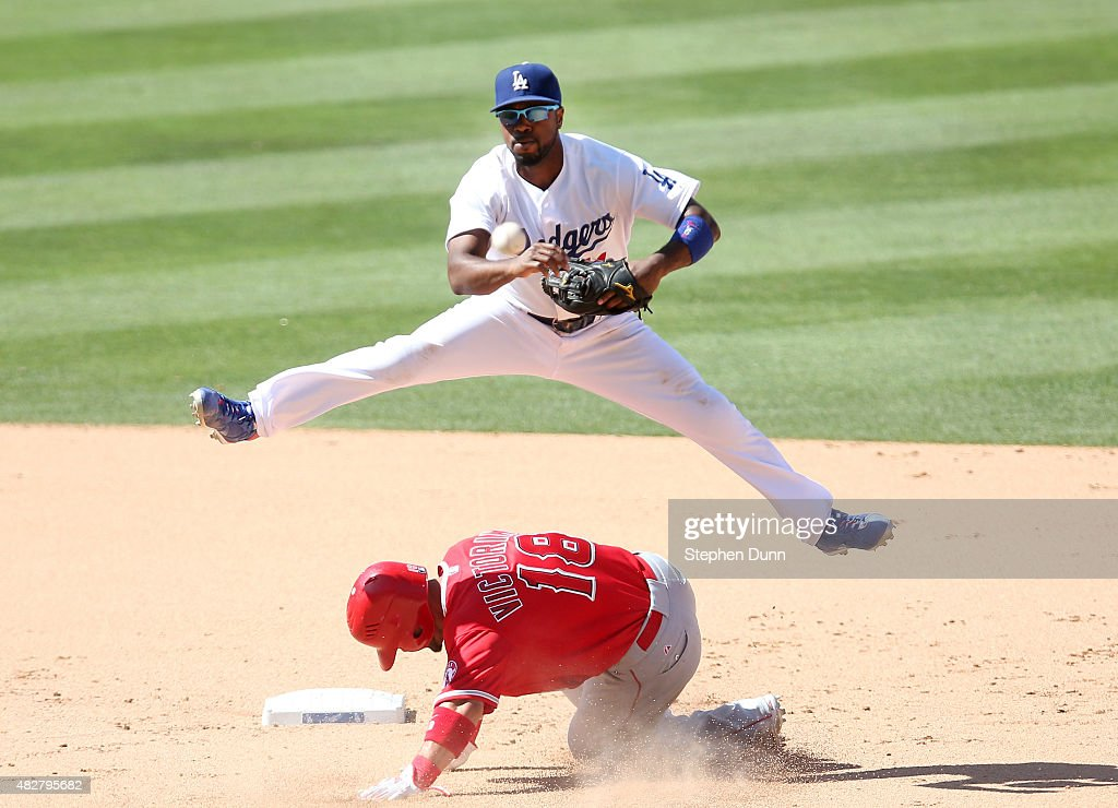 Shortstop Jimmy Rollins #11 of the Los Angeles Dodgers jumps over Shane Vicotrino #18 of the Los Angeles Angels of Anahemi but is too late to turn the double play in the ninth inning at Dodger Stadium on August 2, 2015 in Los Angeles, California. The Dodgers won 5-3 in ten innings.