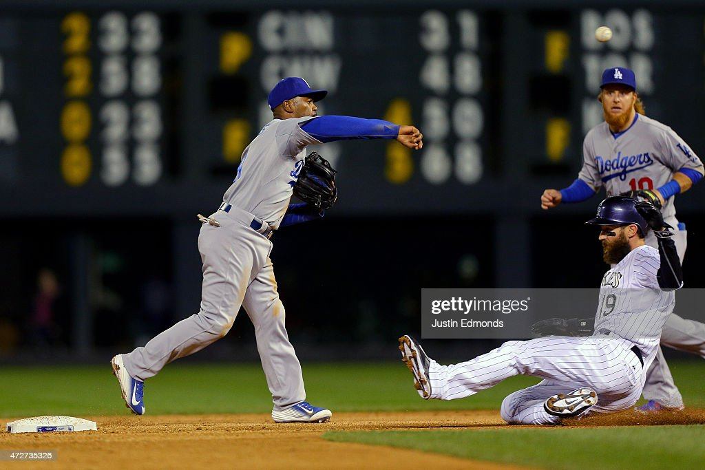 Shortstop Jimmy Rollins #11 of the Los Angeles Dodgers throws to first base to complete the double play to end the third inning as Charlie Blackmon #19 of the Colorado Rockies slides in and second baseman Justin Turner #10 of the Los Angeles Dodgers looks on at Coors Field on May 8, 2015 in Denver, Colorado.