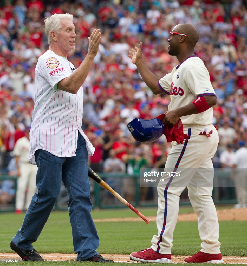 Shortstop Jimmy Rollins #11 of the Philadelphia Phillies hits a single in the bottom of the fifth inning against the Chicago Cubs and is congratulated by former Phillies third baseman Mike Schmidt #20 on June 14, 2014 at Citizens Bank Park in Philadelphia, Pennsylvania. This single makes Jimmy Rollins the all-time Phillies career hit leader with 2,235 hits.