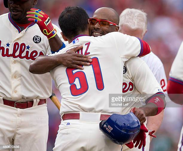 Shortstop Jimmy Rollins of the Philadelphia Phillies hits a single in the bottom of the fifth inning against the Chicago Cubs and is congratulated by...