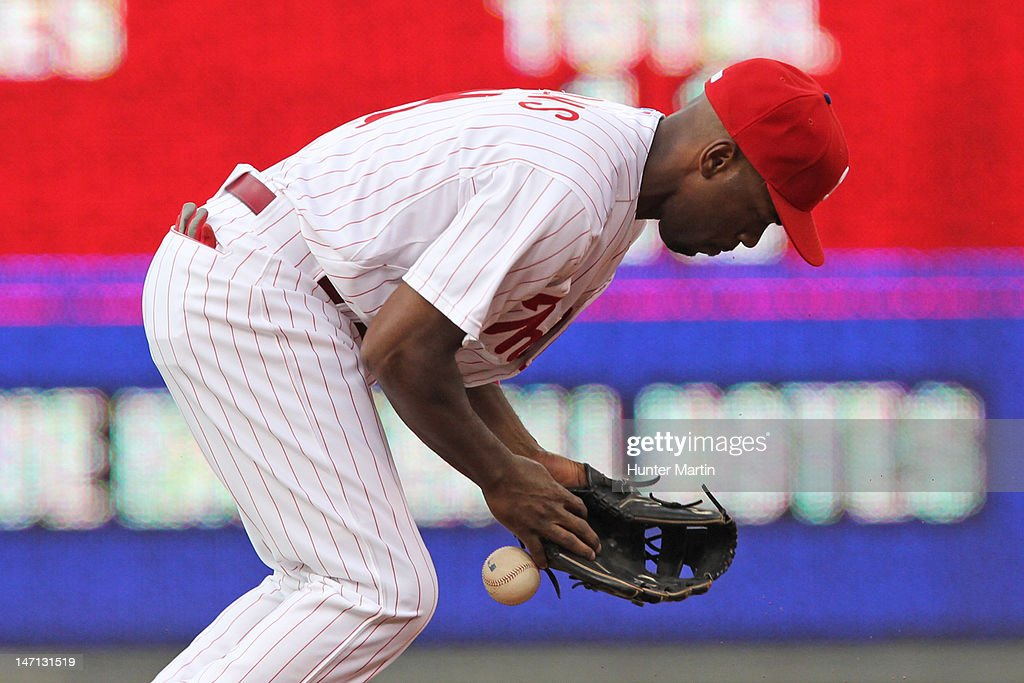 Shortstop <a gi-track='captionPersonalityLinkClicked' href=/galleries/search?phrase=Jimmy+Rollins&family=editorial&specificpeople=204478 ng-click='$event.stopPropagation()'>Jimmy Rollins</a> #11 of the Philadelphia Phillies misplays a ground ball for an error during a game against the Pittsburgh Pirates at Citizens Bank Park on June 25, 2012 in Philadelphia, Pennsylvania.