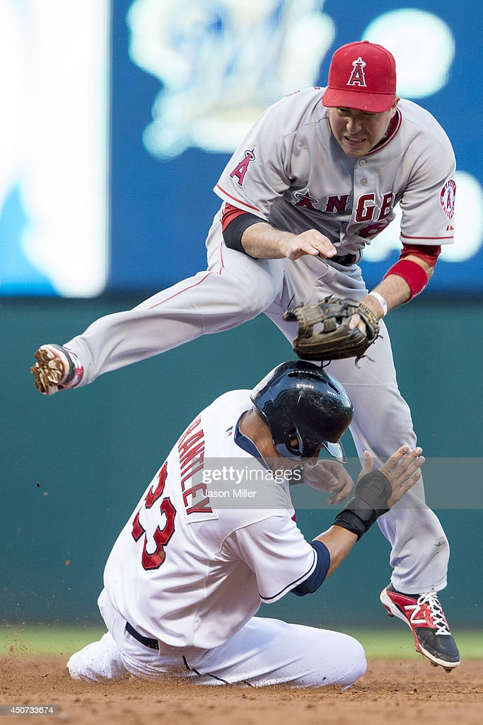 Shortstop <a gi-track='captionPersonalityLinkClicked' href=/galleries/search?phrase=John+McDonald+-+Baseball+Player&family=editorial&specificpeople=215395 ng-click='$event.stopPropagation()'>John McDonald</a> #8 of the Los Angeles Angels of Anaheim jumps over Michael Brantley #23 of the Cleveland Indians after turning a double play to end the third inning at Progressive Field on June 16, 2014 in Cleveland, Ohio.