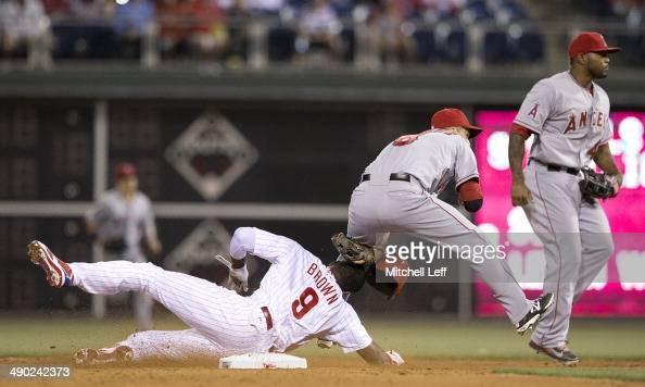 Shortstop John McDonald of the Los Angeles Angels of Anaheim turns the gameending double play with left fielder Domonic Brown of the Philadelphia...