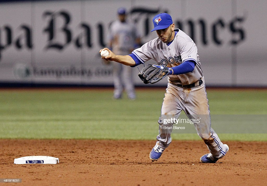 Shortstop Jonathan Diaz of the Toronto Blue Jays briefly stumbles as he makes the throw to first to get the out on James Loney of the Tampa Bay Rays during the fifth inning of a game on April 1, 2014 at Tropicana Field in St. Petersburg, Florida.