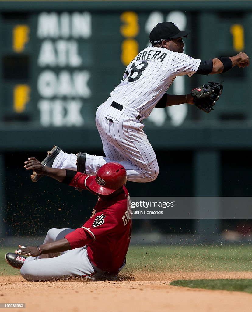 Shortstop Jonathan Herrera of the Colorado Rockies gets upended by a sliding Didi Gregorius of the Arizona Diamondbacks on a double play attempt...