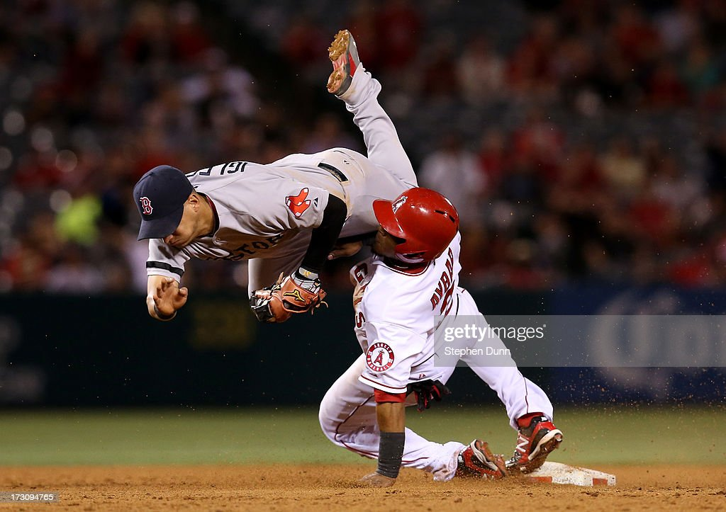 Shortstop Jose Iglesias #10 of the Boston Red Sox flips over <a gi-track='captionPersonalityLinkClicked' href=/galleries/search?phrase=Erick+Aybar&family=editorial&specificpeople=551376 ng-click='$event.stopPropagation()'>Erick Aybar</a> #2 of the Los Angeles Angels of Anaheim after tagging out Aybar at the end of a pickoff play at first in the 10th inning at Angel Stadium of Anaheim on July 6, 2013 in Anaheim, California.