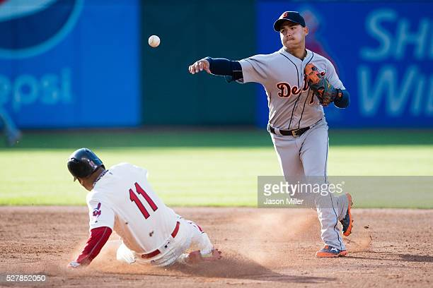 Shortstop Jose Iglesias of the Detroit Tigers throws out Tyler Naquin at first as Jose Ramirez of the Cleveland Indians is out at second for a double...