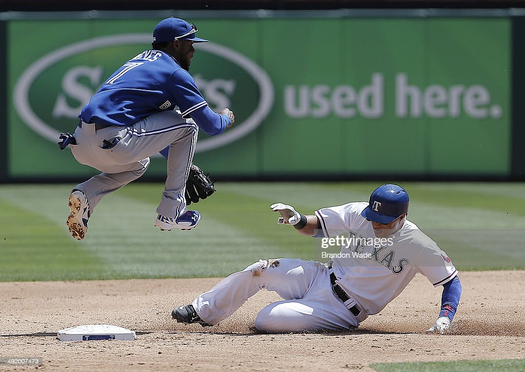 Shortstop Jose Reyes #7 of the Toronto Blue Jays leaps into the air after forcing out Leonys Martin #2 of the Texas Rangers at second during the third inning of a baseball game at Globe Life Park on May 18, 2014 in Arlington, Texas. Reyes throw to first in an attempt to turn a double play, but was unable to.