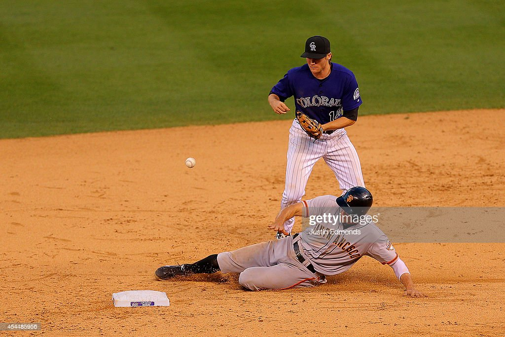 Shortstop <a gi-track='captionPersonalityLinkClicked' href=/galleries/search?phrase=Josh+Rutledge&family=editorial&specificpeople=9541486 ng-click='$event.stopPropagation()'>Josh Rutledge</a> #14 of the Colorado Rockies loses control of the ball while making the transition to throw to first base but is able to convert the out on <a gi-track='captionPersonalityLinkClicked' href=/galleries/search?phrase=Hunter+Pence&family=editorial&specificpeople=757341 ng-click='$event.stopPropagation()'>Hunter Pence</a> #8 of the San Francisco Giants during the ninth inning at Coors Field on September 1, 2014 in Denver, Colorado. The Rockies defeated the Giants 10-9 on a walk-off single by Charlie Blackmon.