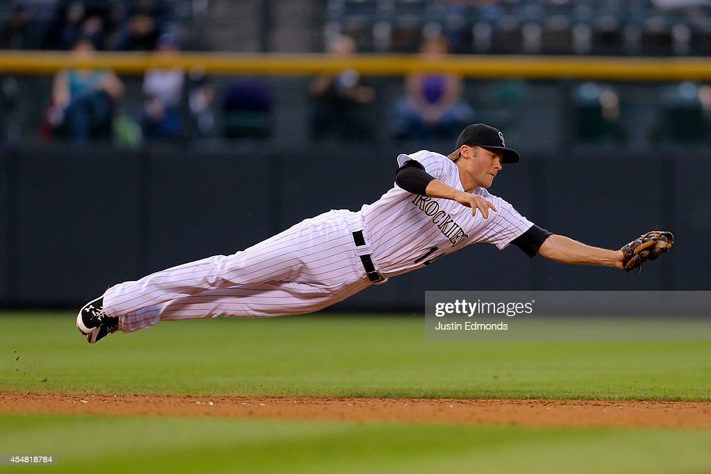 Shortstop Josh Rutledge #14 of the Colorado Rockies makes a diving catch for the first out of the third inning against the San Diego Padres at Coors Field on September 6, 2014 in Denver, Colorado.