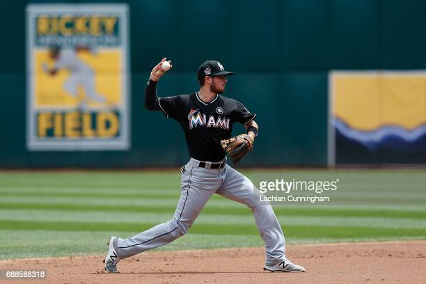 Shortstop JT Riddle of the Miami Marlins throws the ball to first base to get the out of Rajai Davis of the Oakland Athletics in the first inning at...