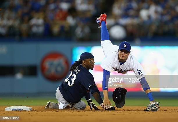 Shortstop Miguel Rojas of the Los Angeles Dodgers falls over Rickie Weeks of the Milwaukee Brewers after forcing him out at second base in the...
