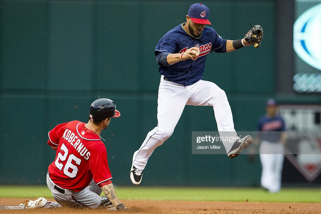 Shortstop Mike Aviles #4 of the Cleveland Indians hops off second base after tagging out Jeff Kobernus #26 of the Washington Nationals to end the top of the second inning at Progressive Field on June 15, 2013 in Cleveland, Ohio.