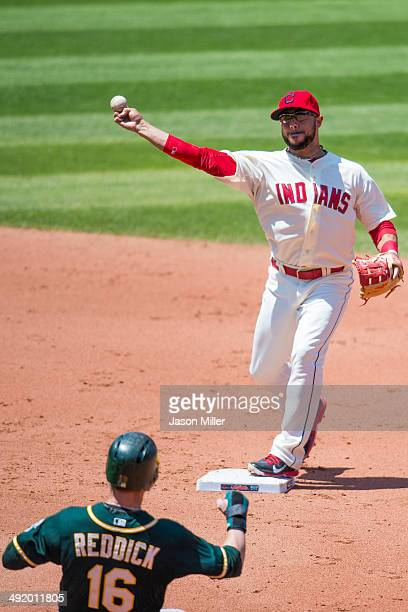 Shortstop Mike Aviles of the Cleveland Indians throws out Alberto Callaspo at first as Josh Reddick of the Oakland Athletics is forced out at second...