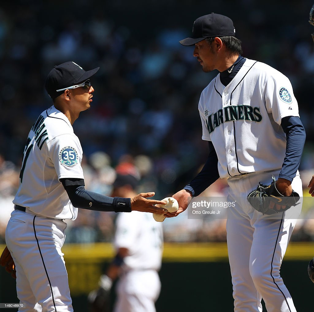 Shortstop Munenori Kawasaki #61 (L) of the Seattle Mariners, hands the rosin bag to starting pitcher Hisashi Iwakuma #18 during a visit to the mound against the New York Yankees at Safeco Field on July 25, 2012 in Seattle, Washington. The Yankees defeated the Mariners 5-2.