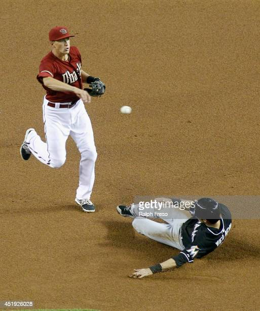 Shortstop Nick Ahmed of the Arizona Diamondbacks throws over Christian Yelich of the Miami Marlins to complete a double play during the first inning...