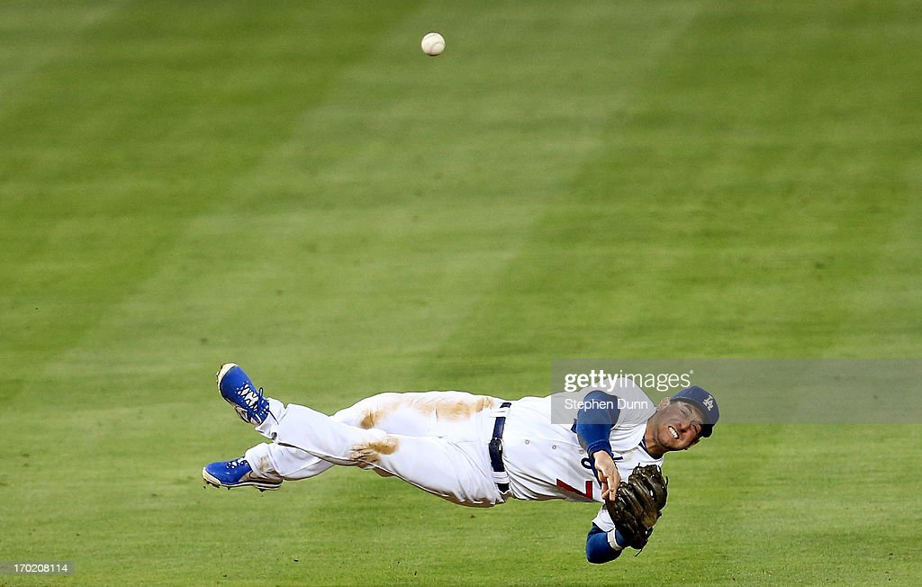 Shortstop Nick Punto #7 of the Los Angeles Dodgers throws to first but is too late to get the out after diving for a ground ball hit by Andrelton Simmons of the Atlanta Braves in the fifth inning at Dodger Stadium on June 8, 2013 in Los Angeles, California.