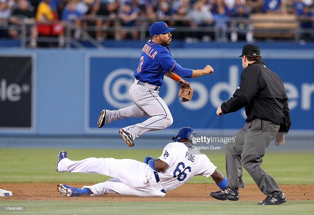 Shortstop Omar Quintanilla #3 of the New York Mets jumps over <a gi-track='captionPersonalityLinkClicked' href=/galleries/search?phrase=Yasiel+Puig&family=editorial&specificpeople=10484087 ng-click='$event.stopPropagation()'>Yasiel Puig</a> #66 of the Los Angeles Dodgers as he turns a double play in the second inning at Dodger Stadium on August 13, 2013 in Los Angeles, California.