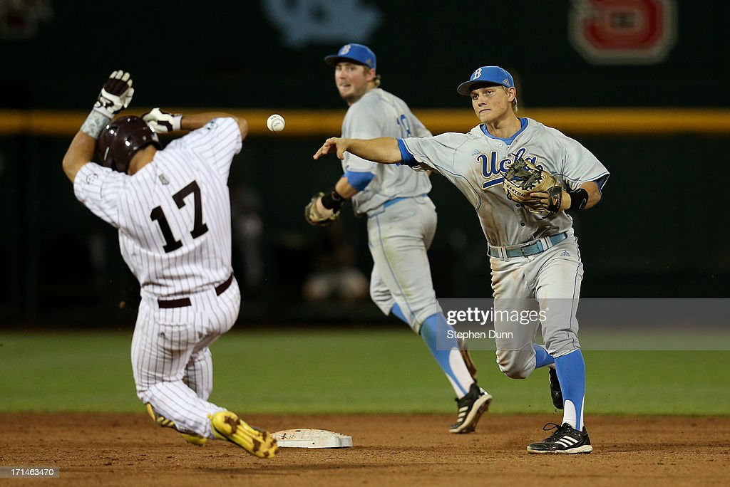 Shortstop Pat Valaika #10 of the UCLA Bruins throws to first to complete a double play after forcing out Nick Ammirati #17 of the Mississippi State Bulldogs during the seventh inning of game one of the College World Series Finals on June 24, 2013 at TD Ameritrade Park in Omaha, Nebraska. UCLA won 3-1.