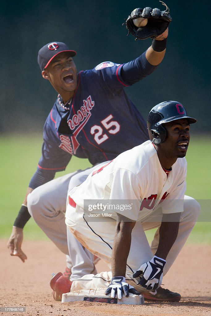 Shortstop Pedro Florimon #25 of the Minnesota Twins reacts as <a gi-track='captionPersonalityLinkClicked' href=/galleries/search?phrase=Michael+Bourn&family=editorial&specificpeople=835742 ng-click='$event.stopPropagation()'>Michael Bourn</a> #24 of the Cleveland Indians is called safe after stretching a double off a fly ball to center during the eighth inning at Progressive Field on August 25, 2013 in Cleveland, Ohio. The Indians defeated the Twins 3-1.
