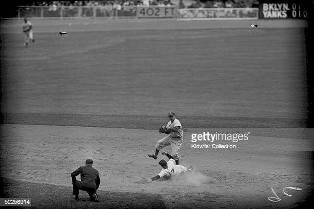 Shortstop Pee Wee Reese of the Brooklyn Dodgers attempts to turn the double play as Enos Slaughter of the New York Yankees slides into second base...