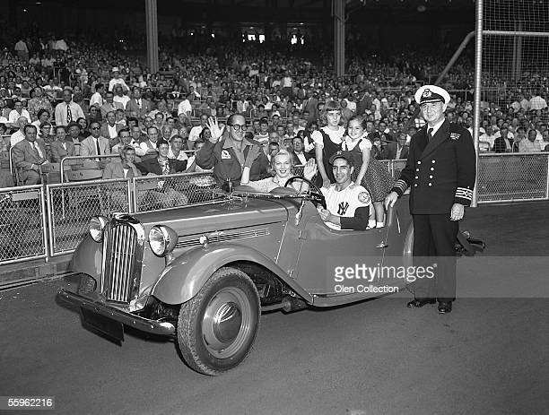 Shortstop Phil Rizzuto of the New York Yankees and his family wave from a new car that was presented to him prior to a game in 1952 at Yankee Stadium...