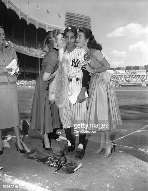 Shortstop Phil Rizzuto of the New York Yankees gets a kiss from members of his family prior to a game in 1952 at Yankee Stadium in New York New York