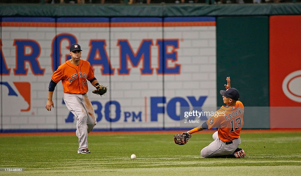 Shortstop Ronny Cedeno #13 of the Houston Astros cannot get to this fly ball as outfielder J.D. Martinez #14 looks on during the game against the Tampa Bay Rays at Tropicana Field on July 14, 2013 in St. Petersburg, Florida.