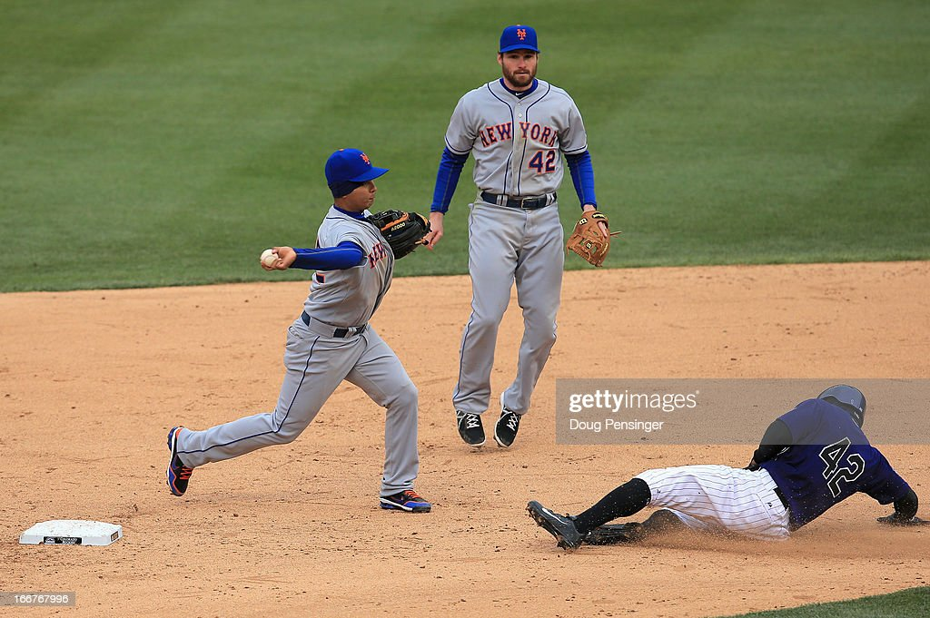 Shortstop Ruben Tejada (L) of the New York Mets turns a double play on Eric Young Jr. (R) of the Colorado Rockies as second baseman Daniel Murphy (C)of the New York Mets follows the play at Coors Field on April 16, 2013 in Denver, Colorado. All uniformed team members are wearing jersey number 42 in honor of Jackie Robinson Day.