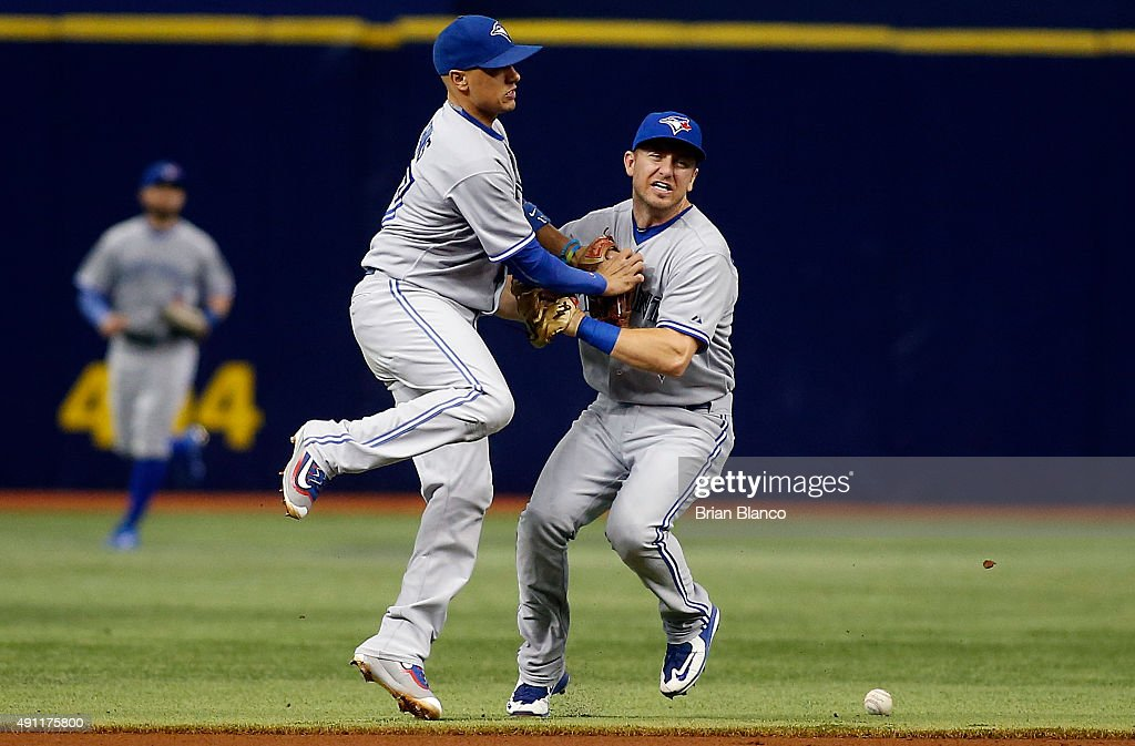 Shortstop Ryan Goins of the Toronto Blue Jays and second baseman Cliff Pennington collide while both attempting to field the infield single by Evan...
