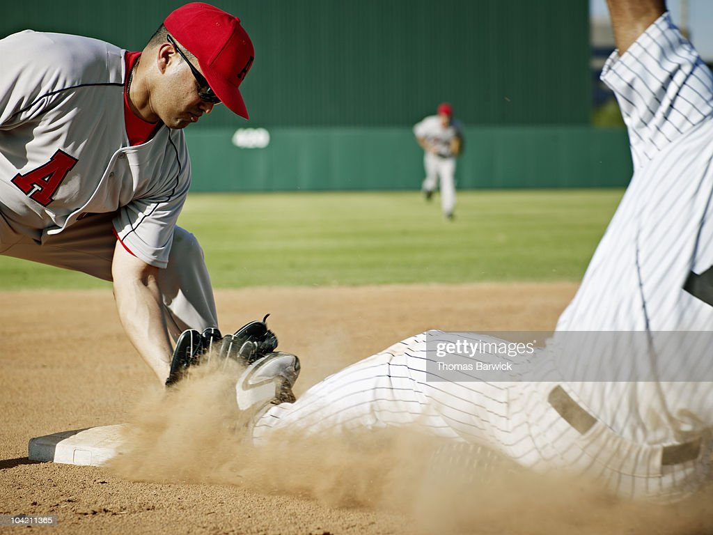 Shortstop tagging player sliding into second base : Stock Photo