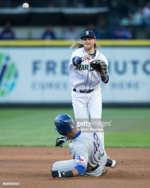 Shortstop Taylor Motter of the Seattle Mariners forces out Carlos Gomez of the Texas Rangers as he turns a double play on a ball hit by Elvis Andrus...