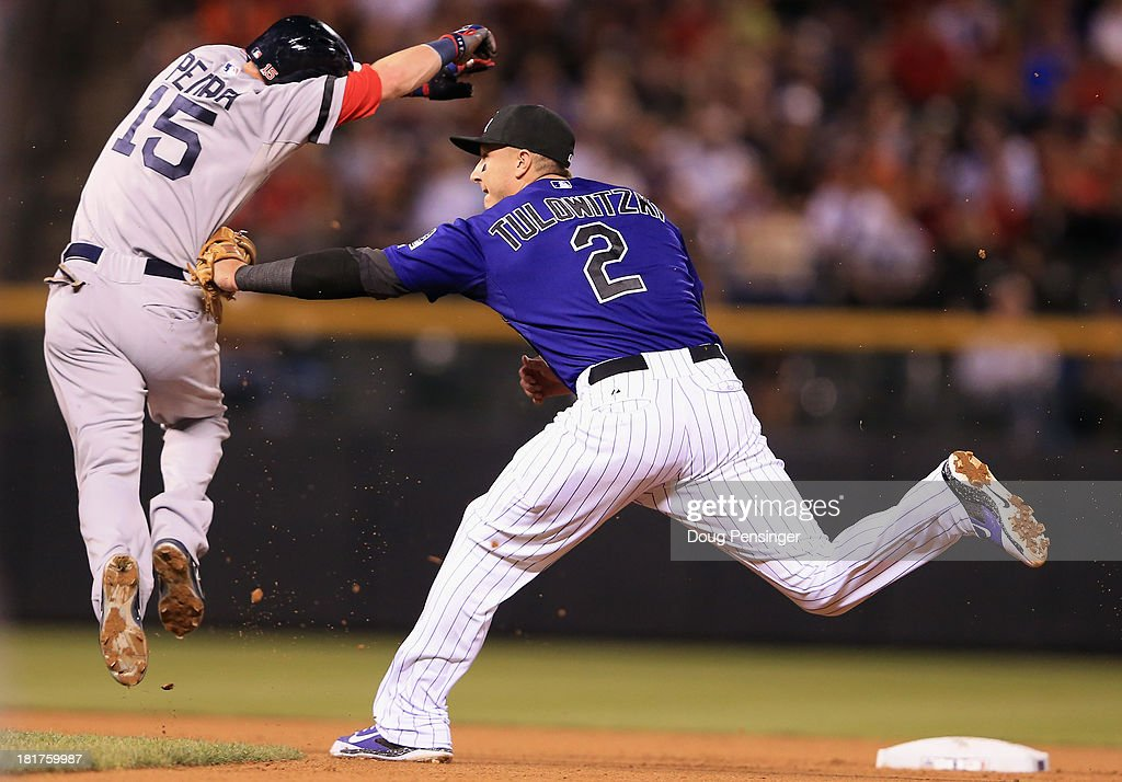 Shortstop <a gi-track='captionPersonalityLinkClicked' href=/galleries/search?phrase=Troy+Tulowitzki&family=editorial&specificpeople=757353 ng-click='$event.stopPropagation()'>Troy Tulowitzki</a> #2 of the Colorado Rockies tags out <a gi-track='captionPersonalityLinkClicked' href=/galleries/search?phrase=Dustin+Pedroia&family=editorial&specificpeople=836339 ng-click='$event.stopPropagation()'>Dustin Pedroia</a> #15 of the Boston Red Sox in a fielders choice on a ground ball by David Ortiz #34 of the Boston Red Sox in the fourth inning at Coors Field on September 24, 2013 in Denver, Colorado.