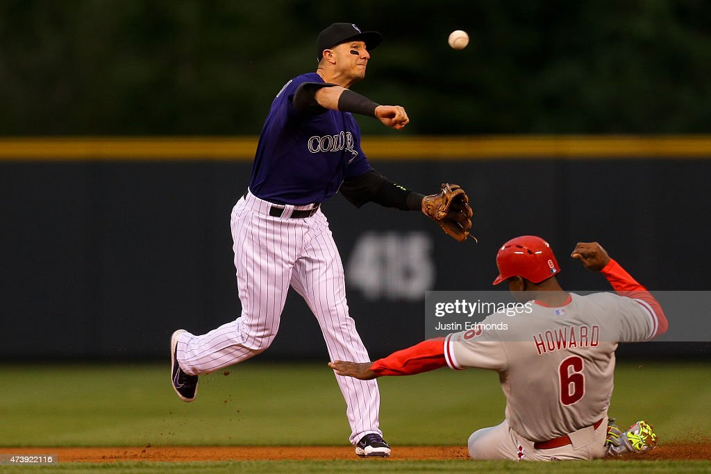 Shortstop Troy Tulowitzki #2 of the Colorado Rockies throws to first base to complete the double play over Ryan Howard #6 of the Philadelphia Phillies at second base at Coors Field on May 18, 2015 in Denver, Colorado.