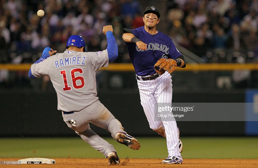 Shortstop Troy Tulowitzki of the Colorado Rockies turns a double play on Aramis Ramirez of the Chicago Cubs on a grounder by Carlos Pena of the Cubs...