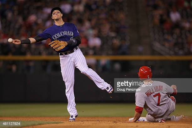 Shortstop Troy Tulowitzki of the Colorado Rockies turns a double play on Matt Holliday of the St Louis Cardinals on a ground ball by Matt Adams of...