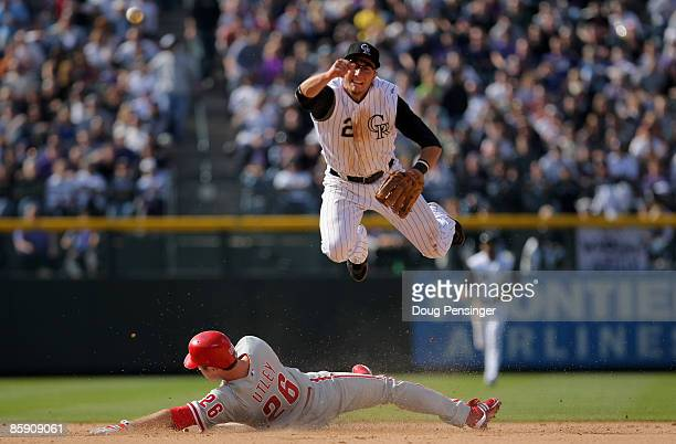Shortstop Troy Tulowitzki of the Colorado Rockies turns a double play on Chase Utley of the Philadelphia Phillies on a grounder hit by Ryan Howard to...