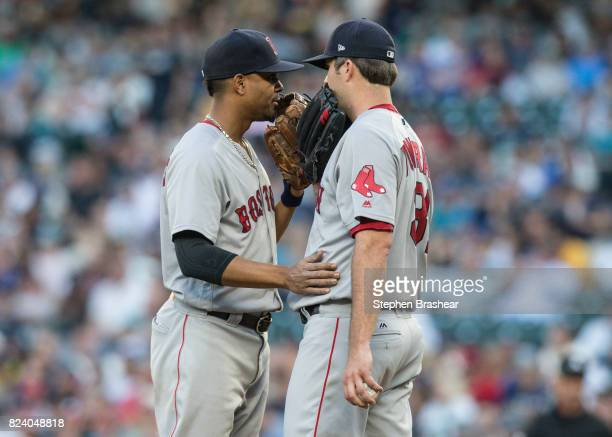 Shortstop Xander Bogaerts left of the Boston Red Sox and starting pitcher Drew Pomeranz of the Boston Red Sox meet at the pitcher's mound during a...