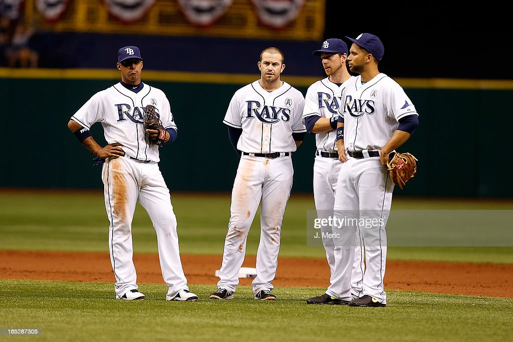Shortstop <a gi-track='captionPersonalityLinkClicked' href=/galleries/search?phrase=Yunel+Escobar&family=editorial&specificpeople=757358 ng-click='$event.stopPropagation()'>Yunel Escobar</a> #11 (left to right), infielder <a gi-track='captionPersonalityLinkClicked' href=/galleries/search?phrase=Evan+Longoria&family=editorial&specificpeople=2349329 ng-click='$event.stopPropagation()'>Evan Longoria</a> #3, infielder <a gi-track='captionPersonalityLinkClicked' href=/galleries/search?phrase=Ben+Zobrist&family=editorial&specificpeople=2120037 ng-click='$event.stopPropagation()'>Ben Zobrist</a> #18 and infielder <a gi-track='captionPersonalityLinkClicked' href=/galleries/search?phrase=James+Loney&family=editorial&specificpeople=636293 ng-click='$event.stopPropagation()'>James Loney</a> #21 of the Tampa Bay Rays chat during seventh inning pitching change during the Opening Day game against the Baltimore Orioles at Tropicana Field on April 2, 2013 in St. Petersburg, Florida.