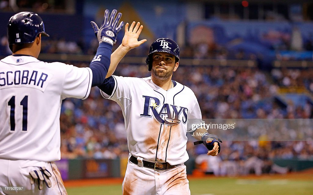 Shortstop <a gi-track='captionPersonalityLinkClicked' href=/galleries/search?phrase=Yunel+Escobar&family=editorial&specificpeople=757358 ng-click='$event.stopPropagation()'>Yunel Escobar</a> #11 of the Tampa Bay Rays congratulates <a gi-track='captionPersonalityLinkClicked' href=/galleries/search?phrase=David+DeJesus&family=editorial&specificpeople=206765 ng-click='$event.stopPropagation()'>David DeJesus</a> #7 after scoring a run against the New York Yankees during the game at Tropicana Field on August 23, 2013 in St. Petersburg, Florida.