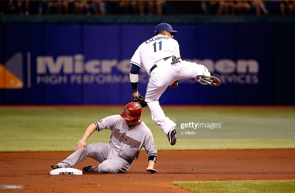 Shortstop <a gi-track='captionPersonalityLinkClicked' href=/galleries/search?phrase=Yunel+Escobar&family=editorial&specificpeople=757358 ng-click='$event.stopPropagation()'>Yunel Escobar</a> #11 of the Tampa Bay Rays turns a double play as <a gi-track='captionPersonalityLinkClicked' href=/galleries/search?phrase=Aaron+Hill+-+Baseball+Player&family=editorial&specificpeople=239242 ng-click='$event.stopPropagation()'>Aaron Hill</a> #2 of the Arizona Diamondbacks attempts to break it up during the game at Tropicana Field on July 30, 2013 in St. Petersburg, Florida.