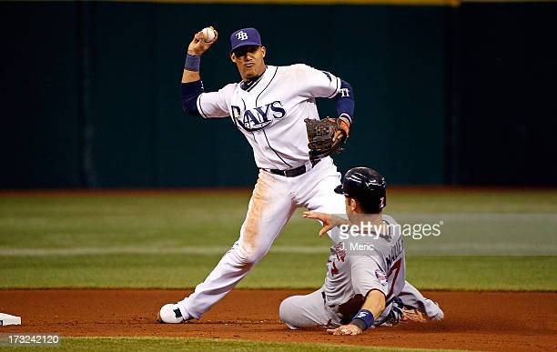 Shortstop Yunel Escobar of the Tampa Bay Rays turns a sixth inning double play as designated hitter Joe Mauer of the Minnesota Twins tries to break...