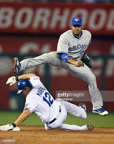 Shortstop Yunel Escobar of the Toronto Blue Jays makes a leaping throw over Mitch Maier of the Kansas City Royals at Kauffman Stadium on April 21...