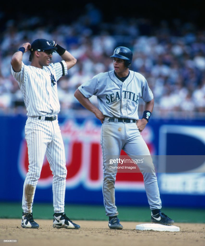 Shortstops Derek Jeter of the New York Yankees and Alex Rodriguez of the Seattle Mariners talk while Rodriguez stands on secondbase during a game in...